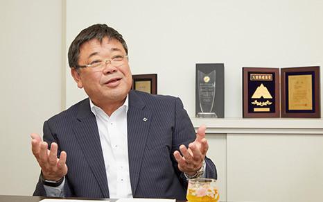 山口毅 社長。建築賞の盾やトロフィーが壁に並ぶ